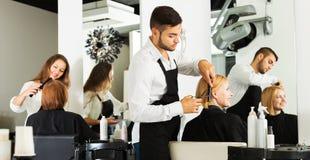 Девушка режет волосы на парикмахерской Стоковое фото RF