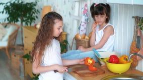 Девушка режет перец в кухне, ее сестра сидит на таблице и ест плюшку, замедленное движение сток-видео