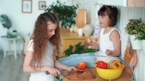 Девушка режет перец в кухне, ее сестра сидит на таблице и ест плюшку, замедленное движение акции видеоматериалы