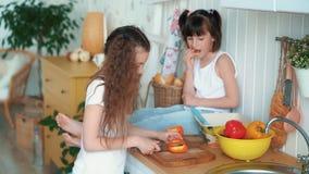 Девушка режет перец в кухне, ее сестра сидит на таблице и ест плюшку, замедленное движение видеоматериал