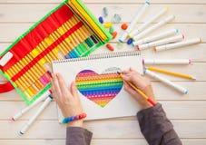 Девушка рисует открытку отметок с сердцем цвета Много яркая метка Стоковое Изображение RF