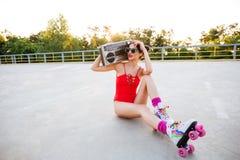 Девушка ролика в музыке красного купальника слушая с рекордным игроком Стоковые Изображения