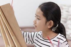 девушка руки держа красный paintbrush рисует изображение дома Стоковые Фотографии RF