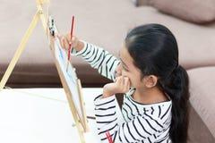 девушка руки держа красный paintbrush рисует изображение дома Стоковое фото RF