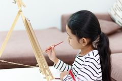 девушка руки держа красный paintbrush рисует изображение дома Стоковое Изображение RF