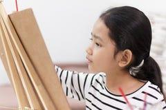 девушка руки держа красный paintbrush рисует изображение дома Стоковая Фотография