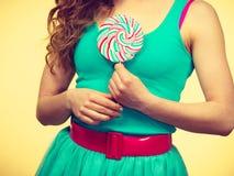 Девушка руки женщины держит конфету леденца на палочке Стоковые Изображения