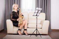 Девушка саксофониста играя на ее музыкальном инструменте в прожитии Стоковые Фото