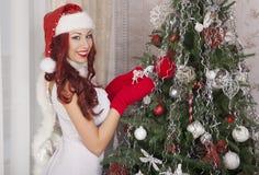 Девушка Санта Клауса украшая рождественскую елку дома красивейший усмехаться Стоковая Фотография