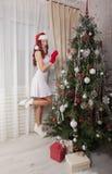 Девушка Санта Клауса украшая рождественскую елку дома красивейший усмехаться Стоковые Изображения