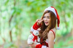 Девушка Санты азиата с медведем Стоковое Изображение