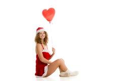 Девушка Санты сидя с сердцем сформировала воздушный шар горизонтальный Стоковая Фотография RF