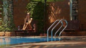 Девушка связывает бассейн подходам к волос около дома сток-видео