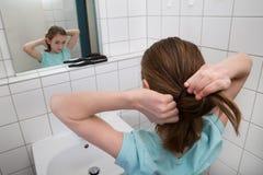 Девушка связывая волосы стоковые изображения