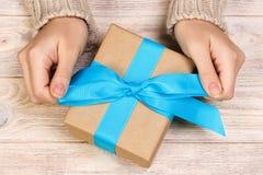 Девушка связывая простой голубой смычок на подарочной коробке Обернутый в простой бумаге ремесла и голубой ленте Последние штрихи стоковые фотографии rf