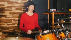 Девушка сидит вниз барабанчики и начинает сыграть сток-видео