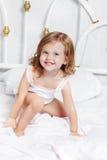 Девушка сидит в кровати Стоковые Изображения RF