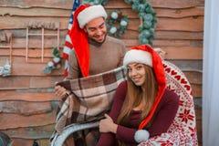 Девушка сидит в стуле, и парень покрывает ее с теплой шотландкой indoors стоковые изображения