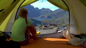 Девушка сидит в шатре и смотрит красивую природу Норвегии видеоматериал