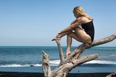 Девушка сидит и ослабляет на ветви дерева, смотрит на море стоковое изображение