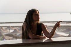 Девушка сидит на баре бара пляжа на зоре Стоковые Изображения RF