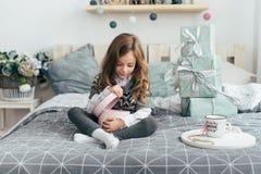 Девушка сидит на кровати и смотрит подарки Стоковая Фотография RF