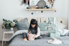 Девушка сидит на кровати и смотрит подарки Стоковые Фото