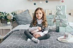 Девушка сидит на кровати и смотрит подарки Стоковые Изображения