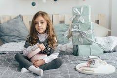 Девушка сидит на кровати и смотрит подарки Стоковое Фото