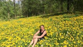 Девушка сидит на луге весны, перерастанном с цветя одуванчиками На голове вены одуванчиков Солнечная весна в сток-видео