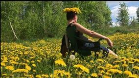 Девушка сидит на луге весны, перерастанном с цветя одуванчиками На голове вены одуванчиков Солнечная весна в видеоматериал