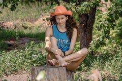 Девушка сидит на пне и смотреть вниз Стоковое Фото