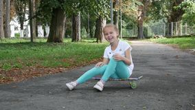 Девушка сидит на скейтборде и езде с боку на бок сток-видео