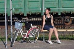Девушка сидит на стенде и слушает к музыке Рядом ее велосипед стоковые изображения rf