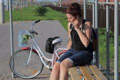 Девушка сидит на стенде и слушает к музыке Рядом ее велосипед В корзине букет цветков стоковые изображения rf