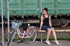 Девушка сидит на стенде и слушает к музыке Рядом ее велосипед стоковая фотография