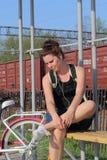 Девушка сидит на стенде и слушает к музыке Рядом ее велосипед стоковое фото rf