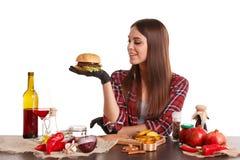 Девушка сидит на таблице с едой, держит бургер и смотрит ее Изолировано на белизне стоковые фотографии rf