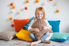 Девушка сидит на ярких подушках Стоковые Изображения RF