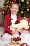 Девушка сидит около ели рождества и играть с медведем, украшением рождества дома, счастливая эмоция, концепция зимнего отдыха Стоковые Изображения RF