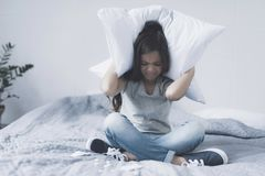 Девушка сидит положив ногу на ногу на кровати, покрывая ее голову с подушкой и хмурясь, перед ее таблетками лож стоковое фото rf