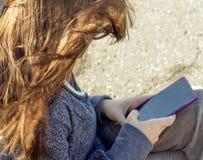 Девушка сидит с большим телефоном в руках цвета сирени стоковая фотография rf