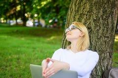 Девушка сидит трава с тетрадью Девушка пользуется виртуальным образованием Минута взятия для того чтобы найти воодушевленность Ст стоковое изображение