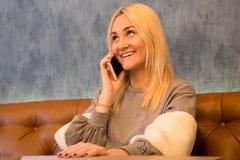 Девушка сидя в кафе и говоря на ее умном телефоне стоковое изображение rf