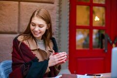 Девушка, сидя в кафе предусматриванном в одеяле, держа кружку и смотря заботливо вниз стоковое фото