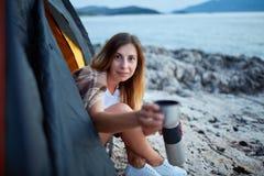 Девушка сидя в шатре, протягивая чашку чаю предлагая к питью Стоковые Фотографии RF
