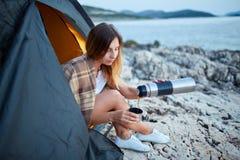 Девушка сидя в шатре, тщательно лить чае от thermos в железную чашку Стоковые Фотографии RF