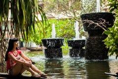 Девушка сидя в экзотическом парке среди фонтанов r E женщина смотря водопад в гостинице стоковое фото rf