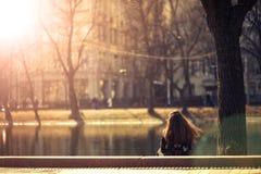 Девушка сидя назад прудом стоковое изображение rf