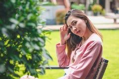 Девушка сидя на деревянный смотреть стула стоковая фотография rf